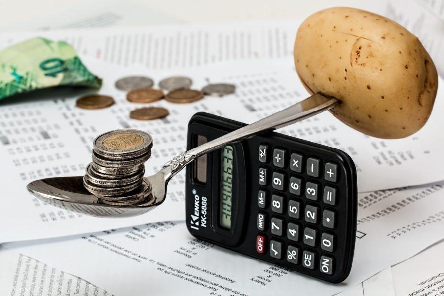 Euromünzen liegen auf einem Löffel, ausbalanciert mitr einer Kartoffel, die am Löffelstiel aufgespießt ist