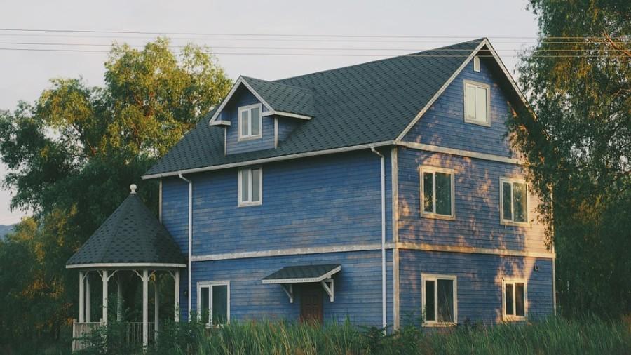 Hellbaues Schwedenhaus im Wald mit weißen Fensterrahmen