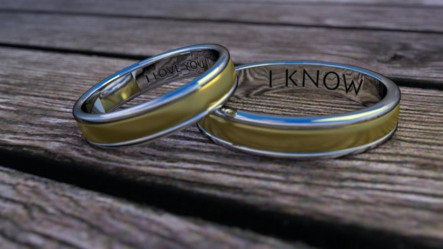 Mattgoldene Eheringe mit der eglischen Inschrift: Ich liebe dich und im anderen Ring: Ich weiß. Nahaufnahme , Ringe auf Holztisch