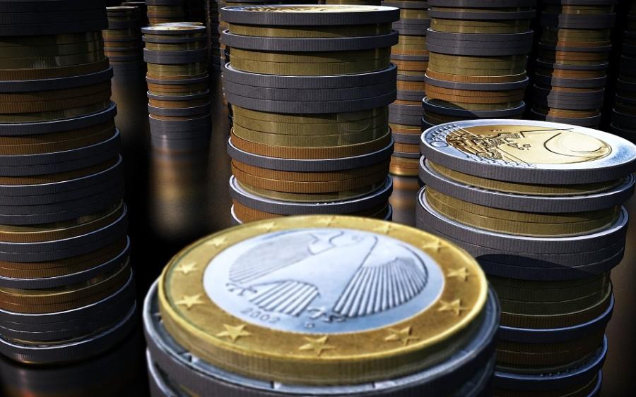 Viele Türme von glänzenden 1 und 2 Euromünzen sehr nah und groß im Vorderund, kleiner werdend nach hinten im Raum