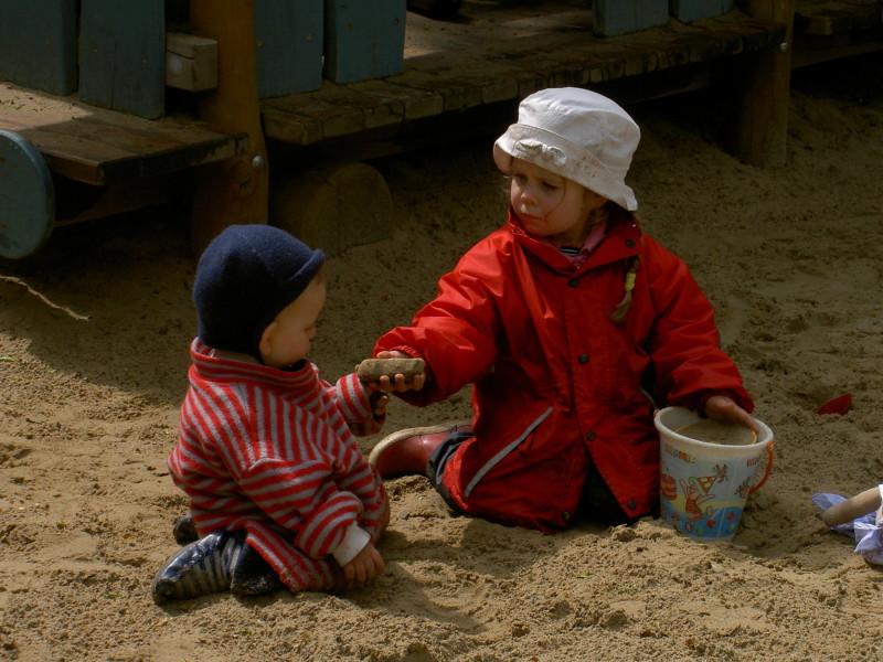 Zwei kleine Kinder backen Kuchen im Sandkasten