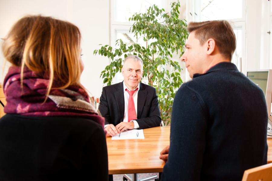 Rechtsanwalt Norbert Maes bei der Paarberatung, lächelnd hinter dem Schreibtisch, im Vordergrund ein Ehepaar im Halbprofil