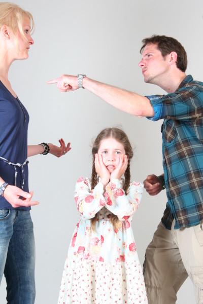 Streitende junge Eltern, links die Frau, rechts der Mann, in der Mitte das verzweifelte Kind, die Hände vor die Ohren gelegt