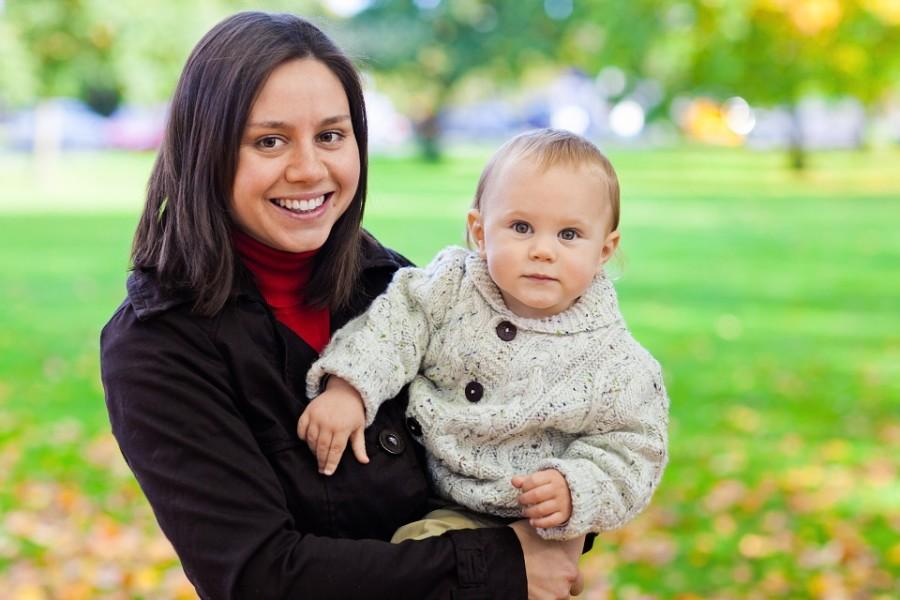 Glückliche Mutter mit Kleinkind auf dem Arm