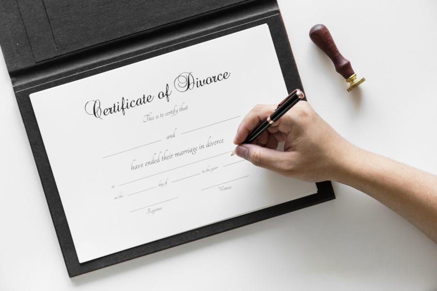Die Scheidungsurkunde liegt auf dem Tisch und wird unterschrieben