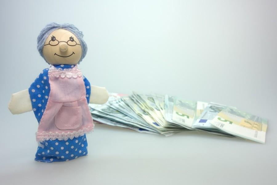 Omapuppe mit rosa Schürze, Geldscheine im Hintergrund