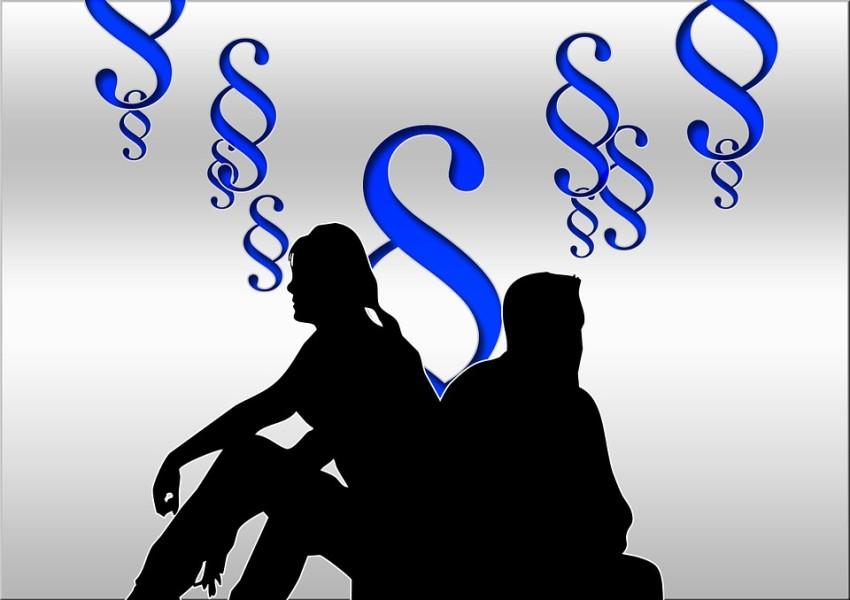 Paar im Schattenriss, sitzend von einander abgewandt, im Hintergrund große blaue Paragraphen