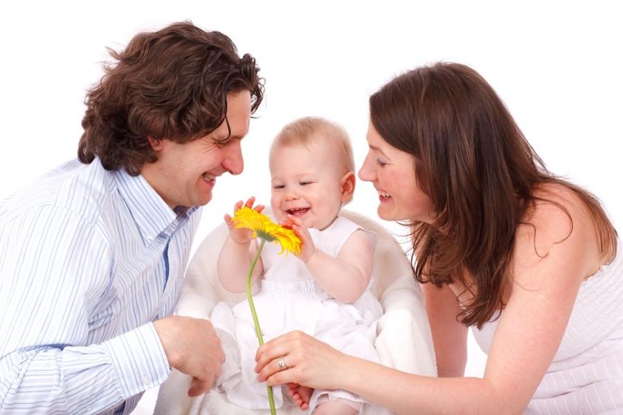 Junge, glückliche Eltern mit Baby in der Mitte, das eine gelbe Blume streichelt