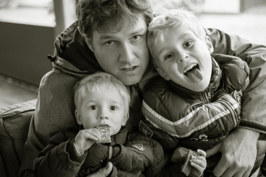 Vater mit zwei Söhnen in Schwarzweiß. Der Ältere streckt die Zunge heraus, der Jüngere knabbert an einem Keks.