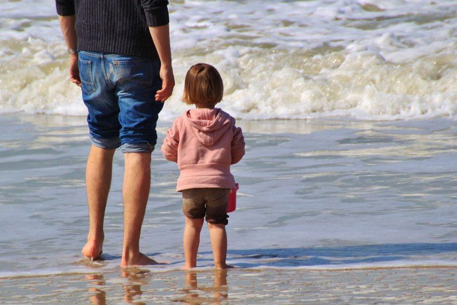 Vater und Kind stehen am am Strand, eine große Wellle kommt