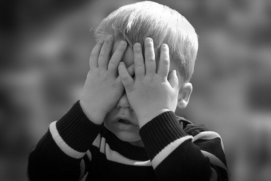 Schwarzweißbild. Kleiner Junge im selbstgestrickten Pullover hält sich die Hände vor das Gesicht, will offbar nicht sehen, was geschieht.