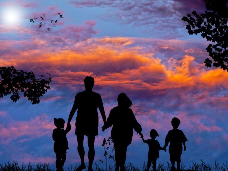 Silhouette einer Familie mit drei kleinen Kindern vor einem Weiten Himmel mit orangefarbenen Wolken