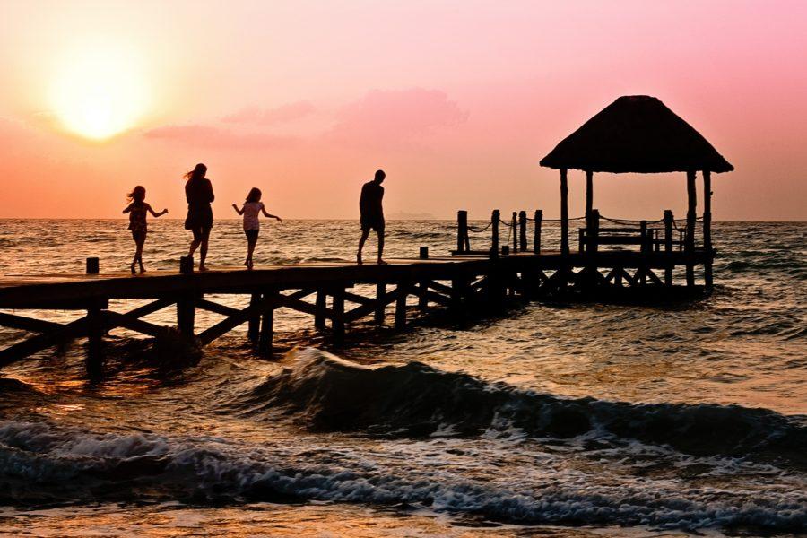 Familie zwei Töchter gehen vor einem Sonnenuntergang in der Karibik auf einen Steg im Meer