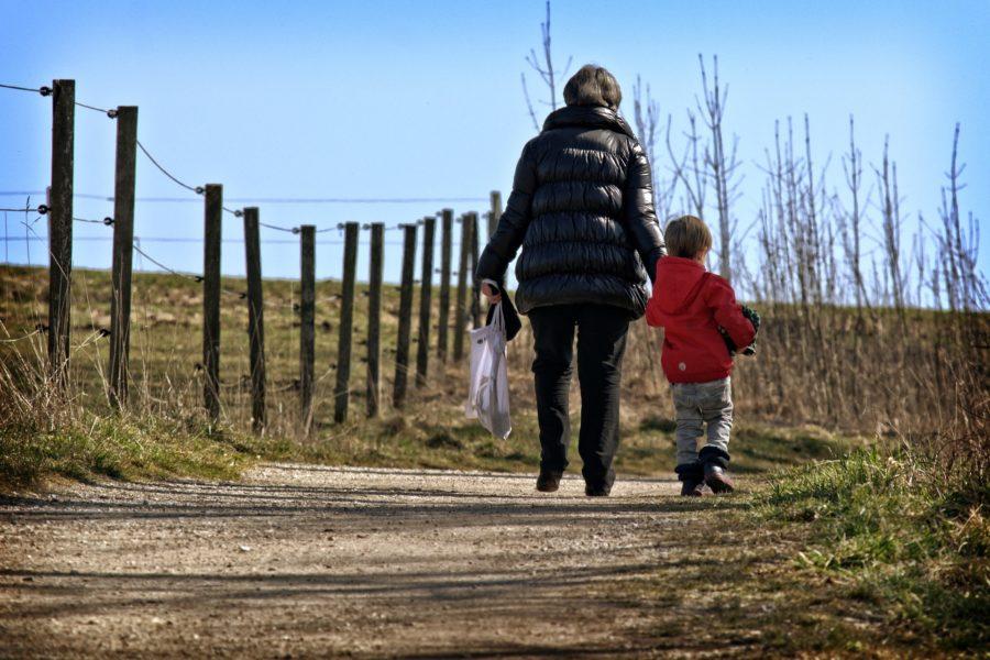 Mutter und Kind von hintren zu sehen gehen einen Sandweg entlang