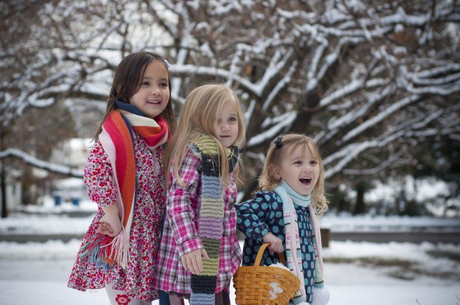 Drei kleine Mädchen nebeneinander von links nach rechts kleiner werdend in Schneelandschaft