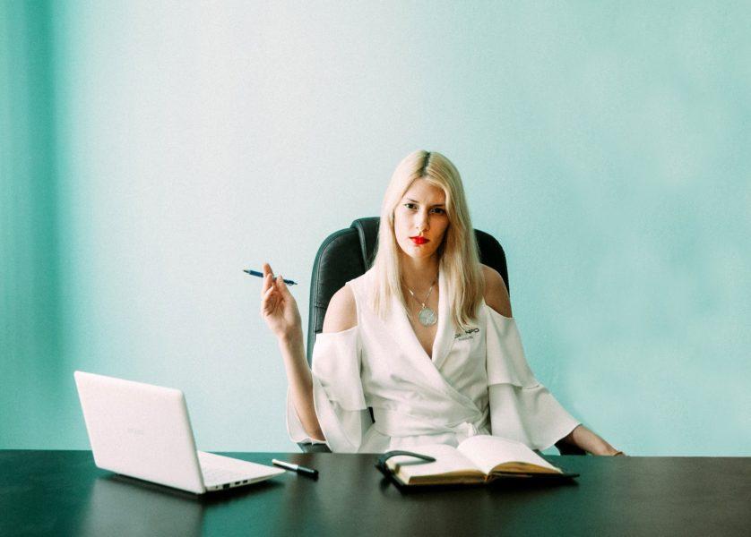 Eine schicke junge blonde Frau, in weiß gekleidet sitzt vor einem weißen Notebook am Schreibtisch