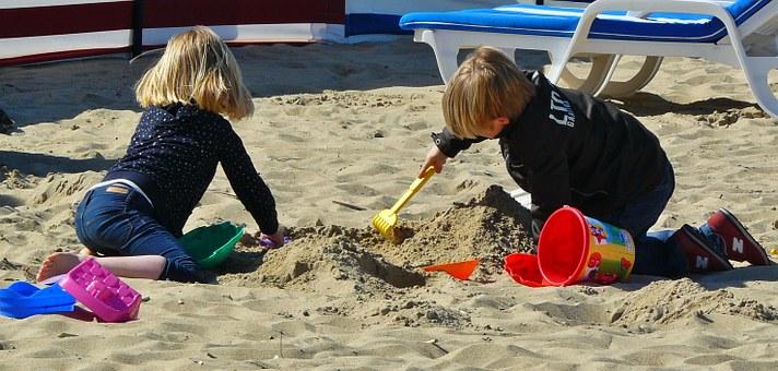 Zwei Kinder Junge und Mädchen spielen am Strand im Sand