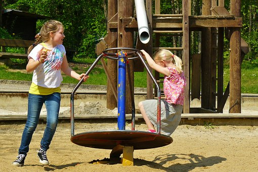 Zwei Mädchen auf dem Spielplatz am Karussell