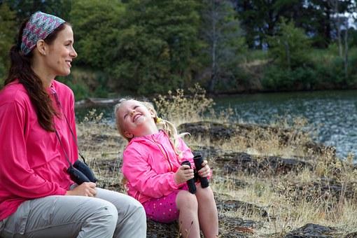 Mutter und kleine Tochter im Wald, beide mit Ferngläsern