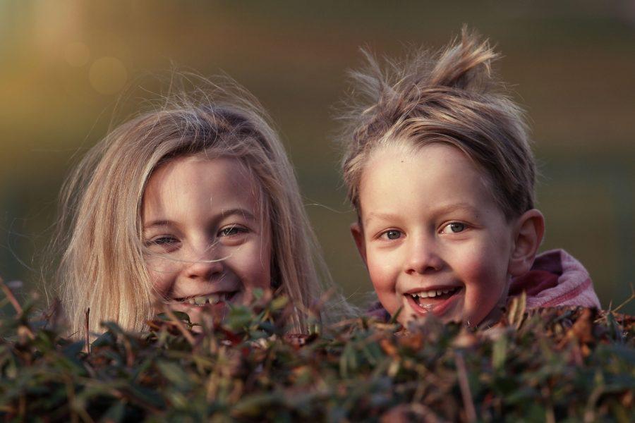 Zwei Mädchen schauen hinter einer Hecke hervor und lachen